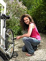 Woman pumping up her bicycle wheel