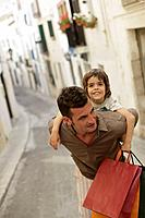 Father carrying son and shopping bags