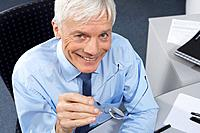 Mature businessman on desk (thumbnail)