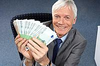Businessman holding money, smiling (thumbnail)