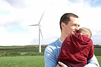 Father holding son on a wind farm