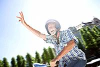 Man on scooter, waving (thumbnail)