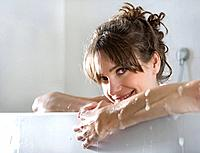 Woman in bathtub, smiling