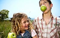 Boy holding apple in teeth with girl