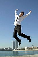 Business man jumping by seafront
