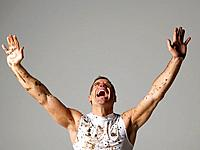 Joyous mud covered man with arms raised