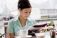 Young Woman Reading a Magazine in a Coffee Shop