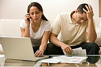 Hispanic couple having difficulty paying bills online