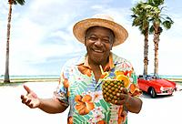 African man holding pineapple drink on tropical beach