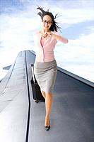 Mixed race businesswoman walking on airplane wing looking at watch