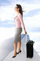 Mixed race businesswoman standing on airplane wing with suitcase