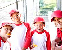 Multi_ethnic boys in baseball uniforms and coach in dugout eating oranges