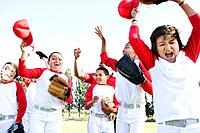 Multi_ethnic boys in baseball uniforms celebrating