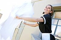 Maid shaking bed sheet outdoors