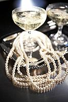 Pearl necklace and champagne on tray