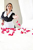 Maid putting flower petals on bed