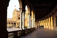 Four people strolling under the arcade of the Plaza de Espana in Maria Luisa Park, Seville, Spain, Europe  The building was designed by Aníbal Gonzále...