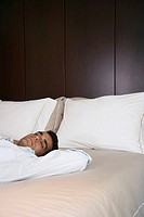 Businessman lying down on bed