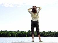 Woman standing on jetty, facing lake, rear view