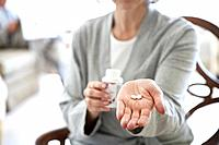 Woman holding hand out with pills in palm, mid section