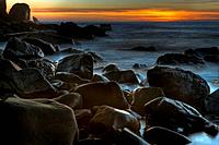 USA, California, Big Sur, black rocks on coast at sunset