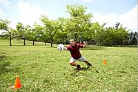 Man diving for soccer ball in goal, smiling