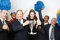 Business people with trophy and pompoms, celebrating, studio shot
