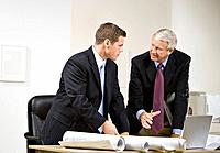 Two businessmen discussing behind desk in office