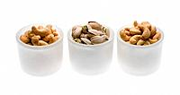 Cashew and pistachio nuts in white bowls on white background