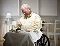Senior man asleep in wheelchair with book on lap