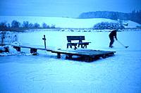 Ice hockey player on frozen lake, Upper Bavaria