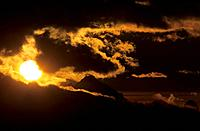 big sun with silhouette of Antelao and dramatic clouds, Dolomites, Venezia, Italy