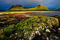 The midnight sun shines on the coastal mountains and beach, A rainbow is forming in the dark clouds, Hadselsand beach, Austvagoya Island, Lofoten, Nor...