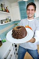 Young man holding a chocolate cake, Munich, Germany