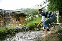 Man splashing with water at a mountain stream, Heiligenblut, Hohe Tauern National Park, Carinthia, Austria