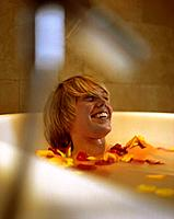 Young Woman in bathtub with rose petals