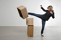 Woman kicking cardboard boxes