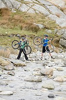 A couple carrying their bikes over a river