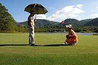 Man playing golf, Caddy, Krimaya Golf Course, Khao Yai National Park, Thailand