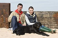 Couple sitting with pet dog at beach