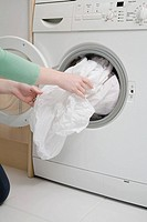 Woman taking sheet from washing machine