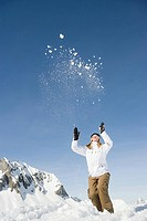 A woman throwing snow