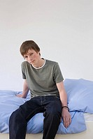 Portrait of a teenage boy sat on a bed