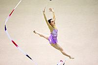Side view of a young woman performing rhythmic gymnastics with ribbon