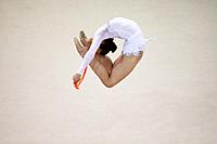Young woman performing rhythmic gymnastics with rope