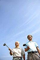 Low angle view of smiling golfers holding golf clubs