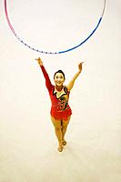 Young woman performing rhythmic gymnastics with hoop