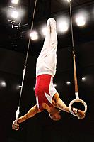 Young male gymnast performing on gymnastic rings