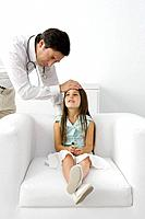 Male doctor feeling young patient's forehead, girl sitting on armchair