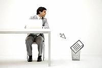 Businessman sitting at desk, looking at computer cursor pointing to document in trash can